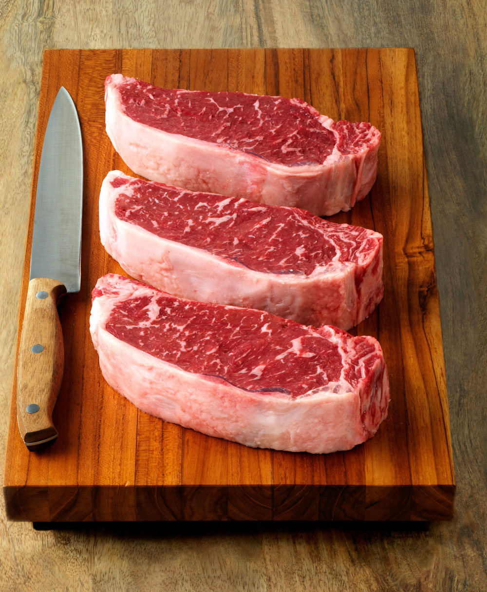 Three Natural Steaks on Cutting Board